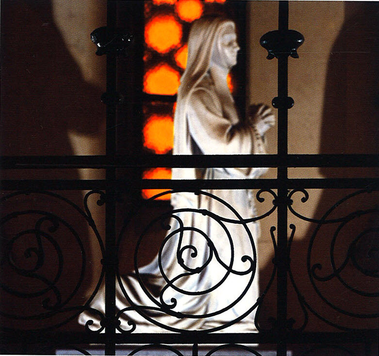 Carved marble statue of St. Bernadette behind a wrought-iron screen.